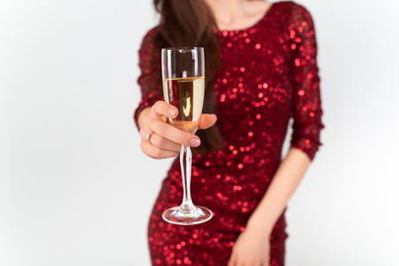 Beautiful brunette woman wearing elegant red dress holding a glass of champagne in her hand on white background Standard-Bild - 112972694