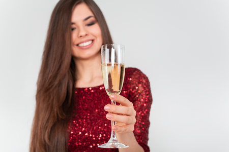 Beautiful brunette woman wearing elegant red dress holding a glass of champagne in her hand on white background Standard-Bild - 112972697