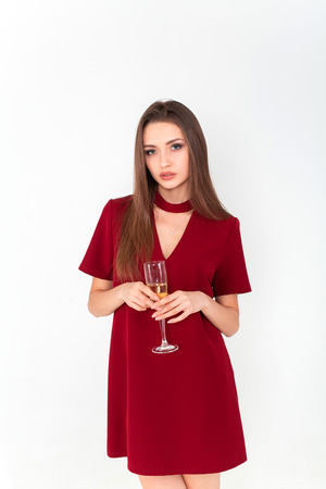 Beautiful brunette woman wearing elegant red dress holding a glass of champagne in her hand on white background Standard-Bild - 112899693