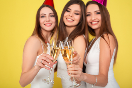 Three young woman in elegant dresses having fun, smiling, dancing and drinking champagne on yellow background. Christmas party celebration concept. Standard-Bild - 112899702