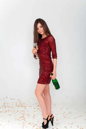 Perfect long legs of young woman in elegant dresses having fun, smiling, dancing and drinking champagne in studio on white background. Christmas party celebration concept. Standard-Bild - 112899714