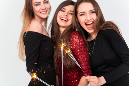 Perfect celebration night concept. Beautiful young women looking at camera and holding sparkler with smile while standing against white background Standard-Bild - 112899717