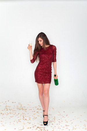 Beautiful brunette woman wearing elegant red dress holding a glass of champagne in her hand on white background Standard-Bild - 112899719