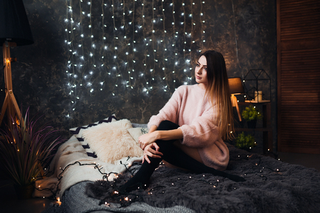 Portrait of sad attractive young woman with tinsel confetti and garland lights celebrating alonein dark room. New years feeling. Merry christmas Standard-Bild - 112899775