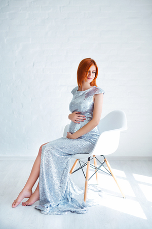 Pregnancy beauty. Beautiful elegant readhead pregnant woman in white dress posing in tender home interior. Banco de Imagens