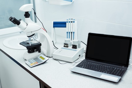 Work place of laboratory worker. Notebook and microscope adjusted and ready for observation