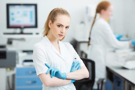 Médico profesional con jeringa médica en las manos, preparándose para la inyección en el laboratorio moderno