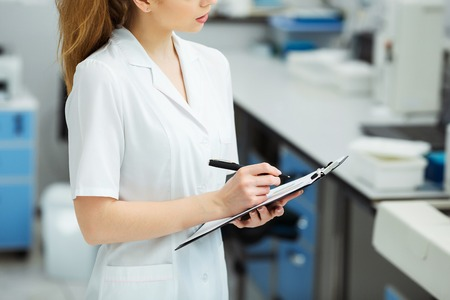Attractive female lab worker making medical research in modern laboratory. Scientist holding documents folder with analysis results.