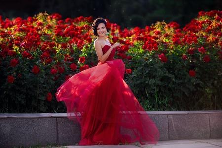 Beautiful girl wearing elegant dress posing near colorful flowers. Art work of romantic woman .
