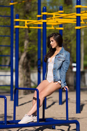 Young pretty smiling fashion tanned sport style woman dressed in swimwear and jeans coat having fun in hot summer