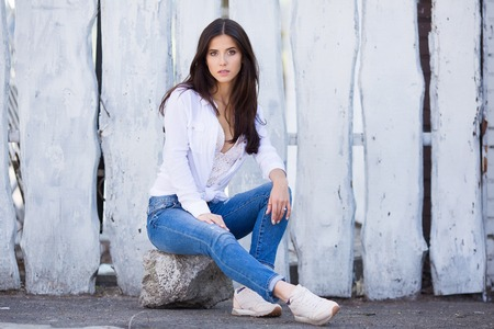 Hipster girl wearing blank white shirt and jeans posing against street wall. Minimalist urban clothing style, street fashion. 스톡 콘텐츠