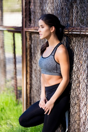 Lifestyle portrait of fitness pretty young woman wearing grey sports bra and black pants. Fresh healthy stylish sport girl posing outdoor. 스톡 콘텐츠