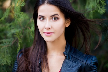 Close up outdoor portrait of young beautiful brunette woman with green eyes and long healthy hair. 스톡 콘텐츠