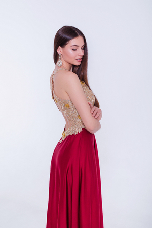 Beauty brunette model woman in evening dress. Beautiful fashion luxury makeup and hairstyle. Seductive girl silhouette on white background. 스톡 콘텐츠