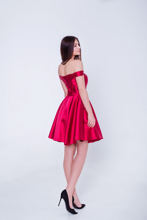 Beauty brunette model woman in cocktail dress. Beautiful fashion luxury makeup and hairstyle. Seductive girl silhouette on white background.