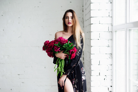 Portrait of beautiful brunette girl with red peonies. Happy boho woman portrait with peony flowers. Creative floral photo.