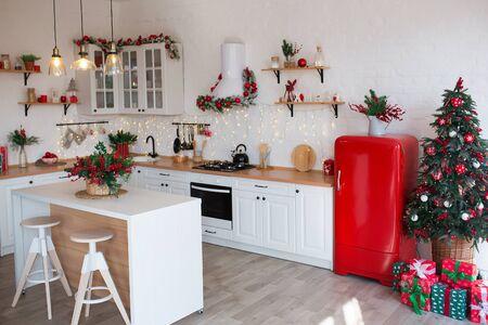 Modernes Kücheninterieur mit Insel, Spüle, Schränken in neuem Luxushaus, das im Weihnachtsstil dekoriert ist.