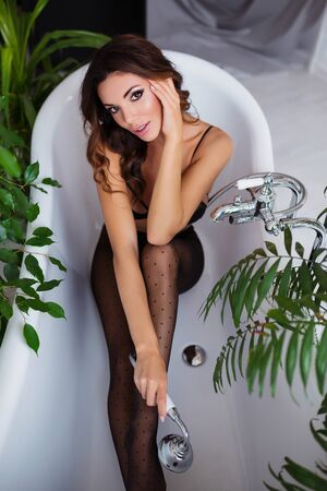 Perfect, seductive body and legs of young woman wearing lingerie and tights shows her hot torso, posing in a sensual way at bathroom