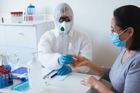 Coronavirus protection concept. Doctor gives mask and sanitizer to patient. Preventive measures against Covid-19 infection. Banque d'images