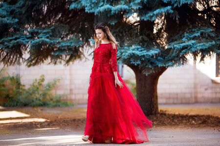 Beautiful young girl with elegant dress and nice smile walking in the street.