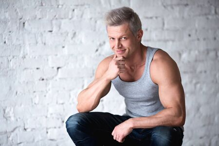 Portrait of confident young man wearing grey shirt. Standard-Bild