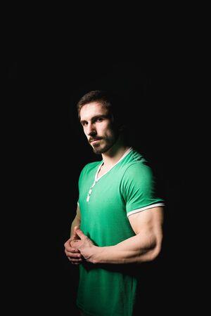 Dark shadow portrait of confident young man wearing black shirt.