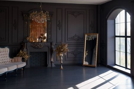 Black room interior with a vintage sofa, chandelier, mirror and fireplace Standard-Bild - 149376658