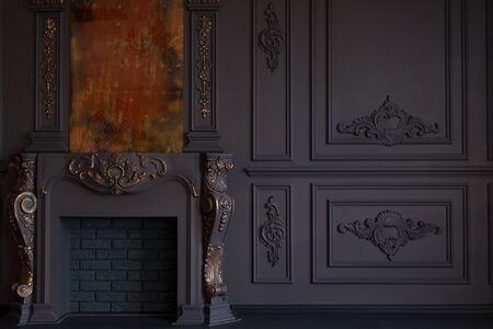 Decorative fireplace, vintage mirror and chandelier in classical black room interior 免版税图像