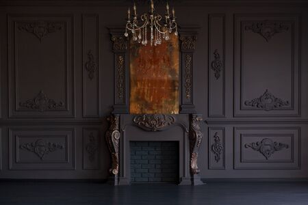 Decorative fireplace, vintage mirror and chandelier in classical black room interior Standard-Bild