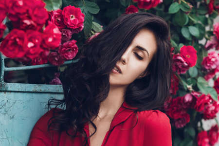 Beautiful portrait of sensual brunette woman close to red roses. Toned image Standard-Bild - 151085047