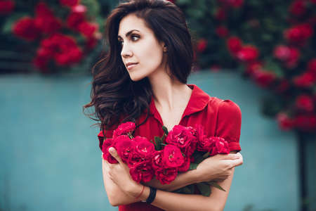 Beautiful portrait of sensual brunette woman close to red roses. Toned image Standard-Bild - 151085050