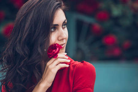 Beautiful portrait of sensual brunette woman close to red roses. Toned image Standard-Bild