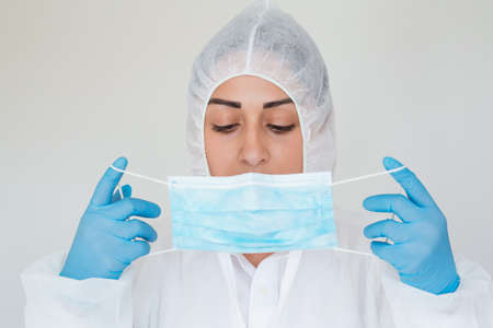 Doctor woman wearing hygienic mask to prevent infection. Coronavirus 2019-nCoV protection concept. Young female wearing protective latex gloves and face mask, close-up. Standard-Bild