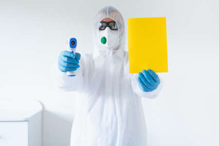 Doctor holding infrared thermometer. Portrait of medical professional in protective clothing measuring contactless fever at Covid-19 test center during coronavirus epidemic.