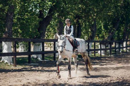 Little Girl in helmet Learning Horseback Riding. Instructor teaches kid Equestrian.
