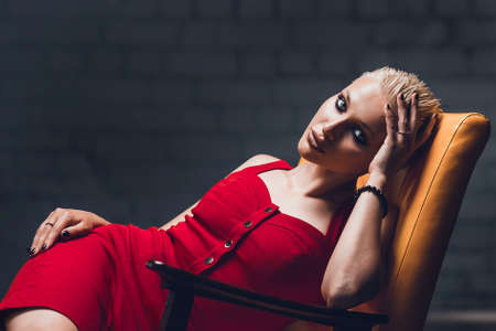 Young woman with blonde hair and a short haircut in a red evening dress lies on the chair.