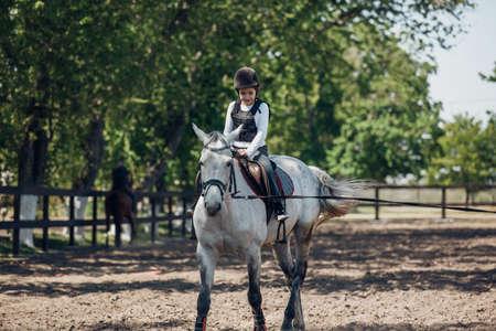 Smiling Little Girl in helmet Learning Horseback Riding. Instructor teaches kid Equestrian.