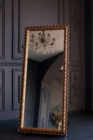 Luxurious gold floor mirror in dark interior Standard-Bild