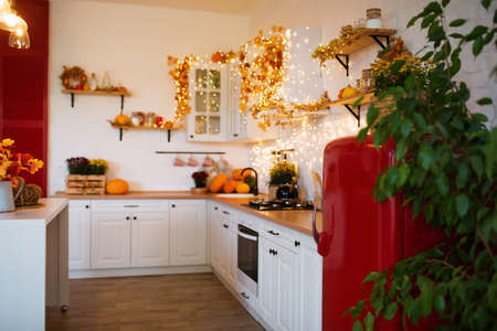 Autumn kitchen interior. Red and yellow leaves and flowers in the vase and pumpkin on light background Standard-Bild