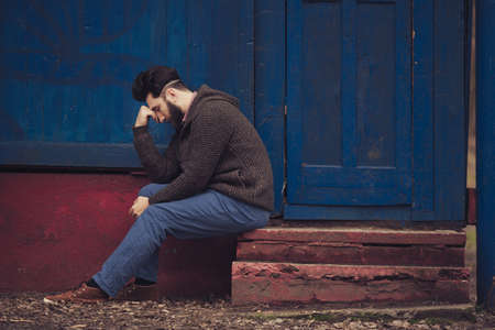 Stressed and upset young man sitting outside holding head with a hand looking down. Human emotion feelings, sad bearded man Standard-Bild