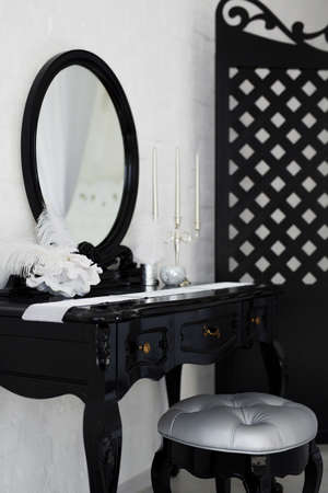 Boudoir table. Details of the interior of the modern black and white bedroom for girls and make-up, hairstyles with a mirror
