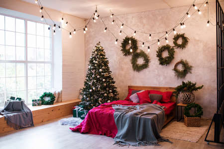 Interior of modern studio living room with comfortable bed decorated with Christmas tree and gifts Standard-Bild