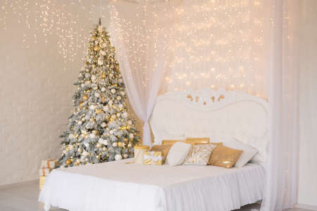 A spacious white light bedroom with a decorated Christmas tree and a garland. New Year interior