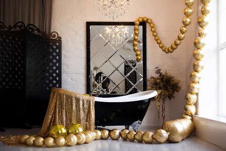 Vintage bright bathroom with black bath and mirror decorated with festive golden balls. Luxury bathroom interior. Standard-Bild