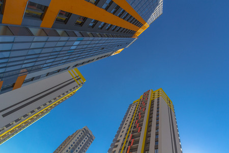 property development: Looking up at multicolour residential buildings with blue ky as a background