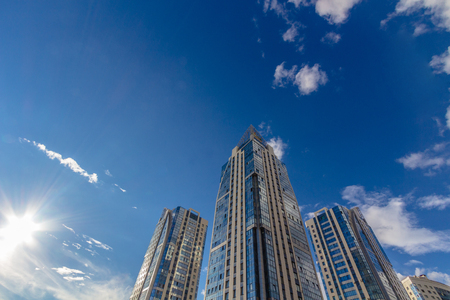 property development: Looking up at tall residential buildings (towers) with cloudy sky and a shinig sun
