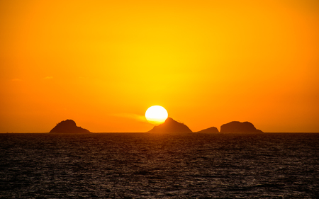 Beautiful golden sunset with the big round sun going down behind the mountain with orange vast sky, dark water of Atlantic Ocean and silhouettes of mountains at Ipanema beach, Rio de Janeiro, Brazil Stock Photo