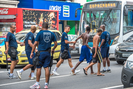 juvenile delinquent: RIO DE JANEIRO, BRAZIL - DECEMBER 30, 2016: Policemen making arrest of criminals and leading them to police cars at Avenida Princesa Isabel during preparation Copacabana to New Year 2017 celebration Editorial