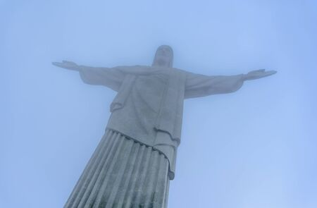 RIO DE JANEIRO, BRAZIL - JANUARY 07, 2017: View of foggy Christ the Redeemer at hazy day, an Art Deco statue of Jesus Christ, one of the New Seven Wonders of the World