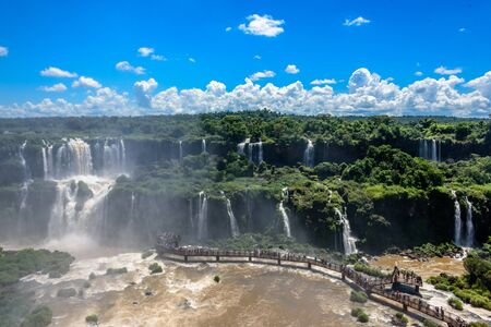 Aerial view of waterfalls cascade of Iguazu Falls with extensive tropical forest and vertical clouds in Iguacu National Park, UNESCO World Heritage Site, Foz de Iguacu, Parana State, Brazil